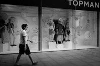 Mężczyzna przechodzący obok sklepu