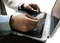 Mężczyzna z kartą kredytową przed komputerem